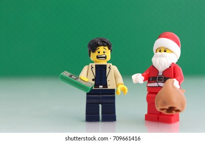 Colorado, USA - September 5, 2017: Studio shot of  LEGO guy holding money with scared look on his face by Santa.