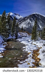 Colorado winter landscape of high mountain peaks and alpine forest covered with freshly fallen snow with river running up the valley