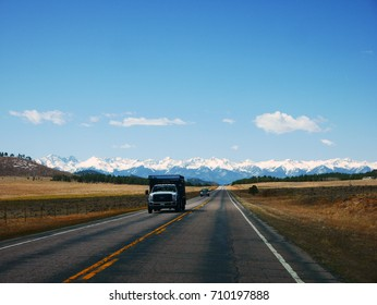 COLORADO/USA - April 14, 2017: A truck running on an empty road in Colorado with a snow mountain in the background