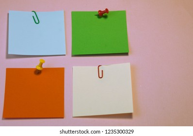 color-coded filing system for records, buttons, and paperclips lying on pink background