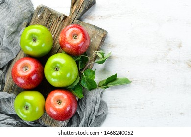 Colored apples on a white wooden background. Fruits. Top view. Free space for text.