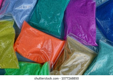 Colored background of small packages of sand