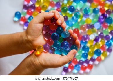 Colored balls of hydrogel in children's palms. Sensory experiences