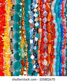 Lot of colored beads from different minerals and stone background
