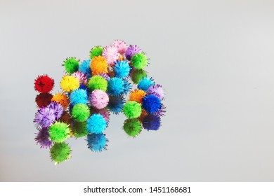 Colored beautiful pompons on a gray background. Assortment of pompons on the mirror surface.