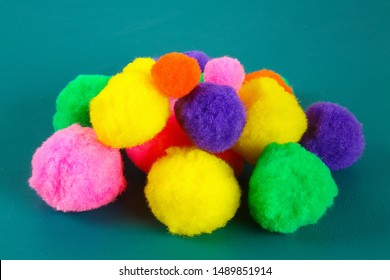 Colored beautiful pompons on a teal background. Assortment of pompons. DIY craft.