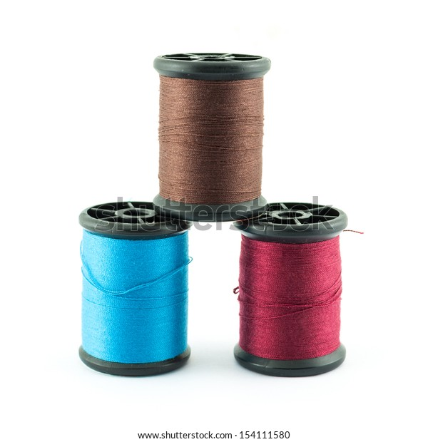 colored bobbins of silk threads on a coils isolated on white