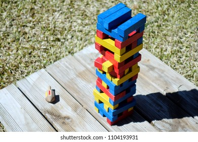 Colored bricks stacked in tower on wooden board in bright sunshine.