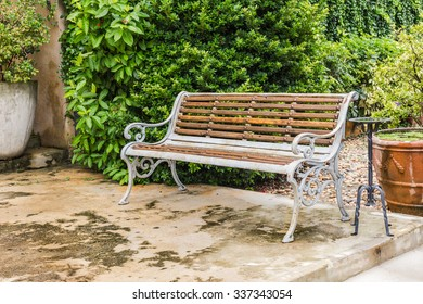 Colored brown bench in a green park with trees, concrete urn in the park
