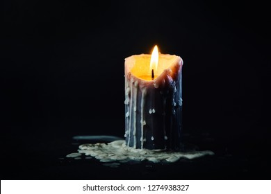 colored candle with drips of wax burns in the dark on a black background in smoke with dripping wax