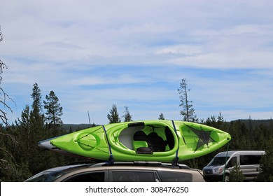 Colored canoe strapped to a roof rack on top of a car