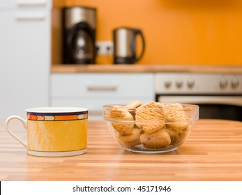 colored ceramic cup of tea and transparent bowl with cookies are on the kitchen table