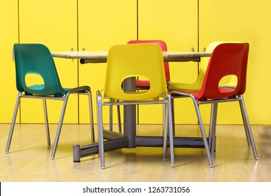 colored chairs around a table in a class of a nursery school