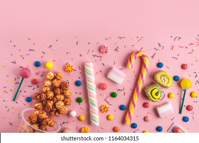 Colored, children's, unhealthy candy, marmalade, marshmallow, caramel popcorn, chupa-chups on a pink background. A table full of sweets. Top view, copy space