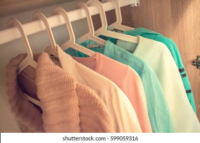 Colored clothes on a hanger in the closet. Trend colors. Pink and Mint look.Fashionable wardrobe. Shopping.