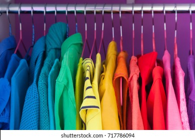 Colored clothing of all colors of the rainbow / spectrum hanging in the wardrobe.