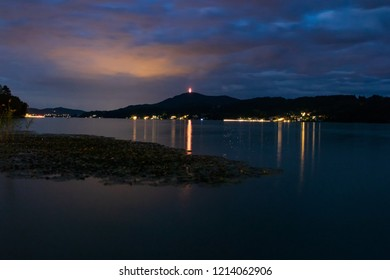 colored clouds over lake with a pier in the middle and reflection in the water. Captured on Woerthersee, Kaernten, Austria.