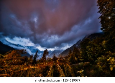 Colored clouds at sunset in mountains landscape with forest in foreground