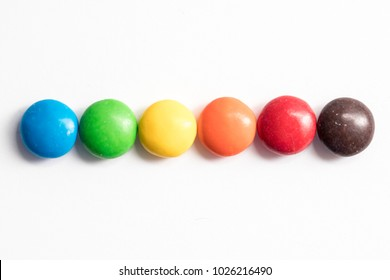 Colored coated chocolate candy similar to m&ms on a white background