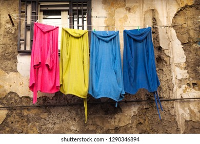 Colored cotton clothes hanging on clothesline for drying against the background of old ruined wall in the city of Naples (Napoli), Italy