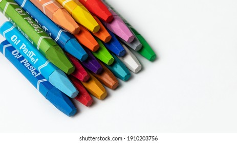"""colored crayons with the inscription """"oil pastel"""" for drawing on a white table. a set for a young artist. the concept of creativity. top view. selective focus"""