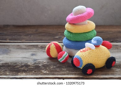 Colored crochet racing car and pyramid from colored rings. Toy for babies and toddlers to learn mechanical skills and colors. Handmade crafts. DIY concept.