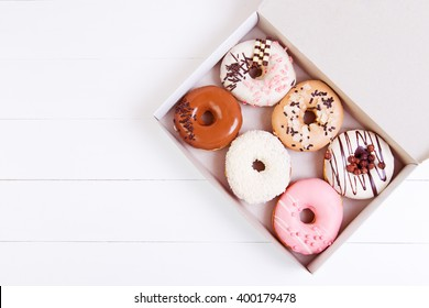 Colored delicious donuts with sprinkles in a box on a white wooden background