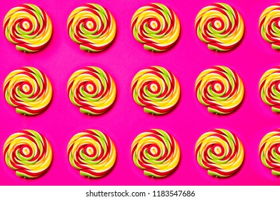 Colored, different sweets, lollipops, marshmallows, caramel popcorn on a pink background.Top view, sweets concept