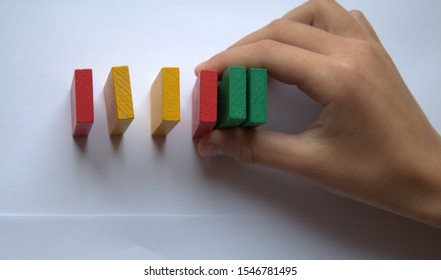 Colored dominoes are on the table. The boy's hand holds wooden blocks that had they not fallen. The view from the top. Colorful: red, green and yellow toys.