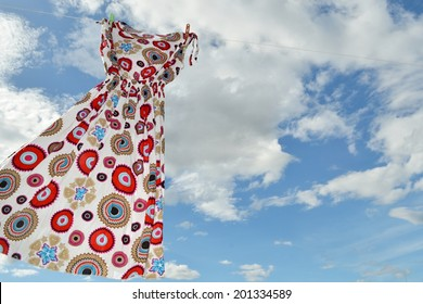 Colored dress hanging on a clothesline in front of cloudy sky