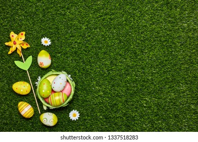 Colored easter eggs and decorative flower on a green grass background. Top view with copy space. Greeting card, Easter background