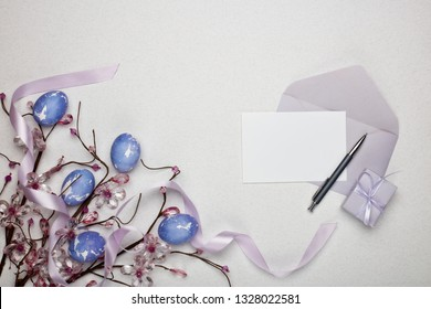 Colored easter eggs, gift box, decorative flowers and blank sheet with envelope  on a lilac  background. Top view with copy space. Greeting card, Easter background