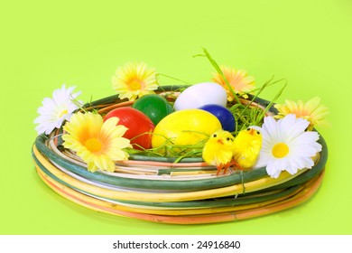 Colored Easter eggs in the nest decorated with daisies and chicken
