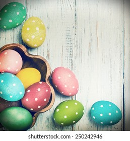 colored Easter eggs on wooden background. Focus on blue wooden background. toned photo