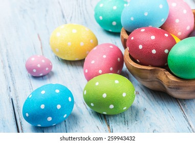 colored Easter eggs on wooden background. Focus on a green egg
