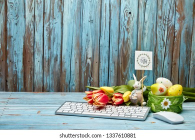 Colored easter eggs, easter rabbit,  spring flowers, computer keyboard and mouse on a wooden  background with copy space. Greeting card, Easter background
