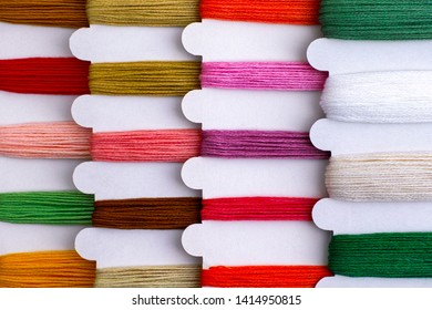 Colored embroidery threads on spools in a row ready for cross stitch. Close-up.
