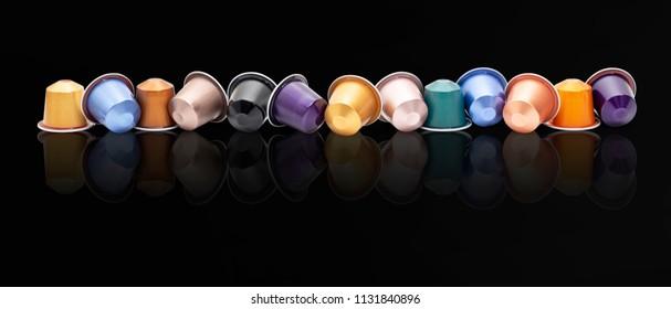 Colored espresso capsules on black background