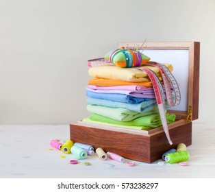 Colored fabric folded stack. Needle bed, scissors, measuring tape. Beige background.