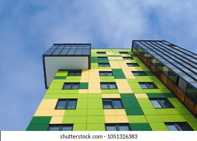 Colored facade wall of a modern residential building with a view from the bottom up against the sky.