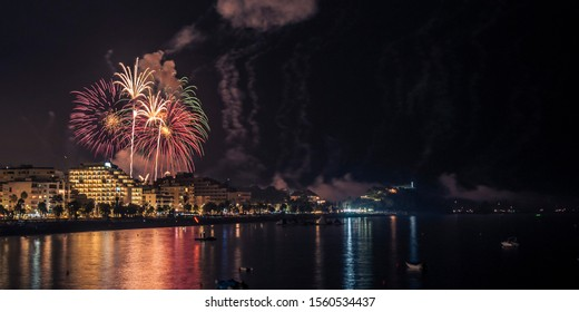 Colored fireworks at night over the sea with light reflected in the water