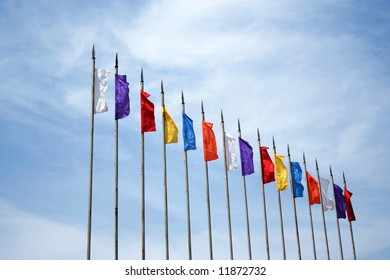 Colored flags on sky background