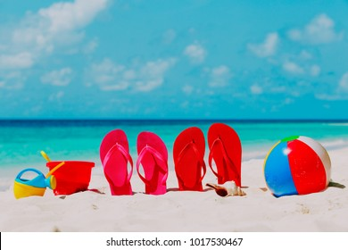 Colored flip-flops, toys and diving mask at beach