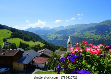 Colored flowers on the balcony of an Austrian house with valley and mountains out of focus in the background shot with a shallow depth of field