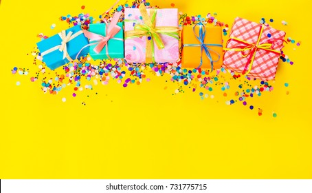 Colored gift boxes with colorful ribbons. Yellow background. Gifts for Christmas or birthday.