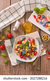 Colored gnocchi with vegetables and sweet corn.