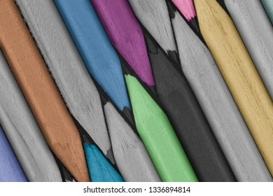 Colored and grey pencils close-up on black background. Macro photo.