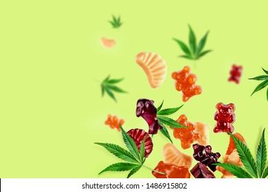 Farbige Gummis fliegen mit Cannabisblättern. Kauen Süßigkeiten, Gummi mit CBD Öl und THC. Farbiger kreativer Hintergrund, Minimalismus.