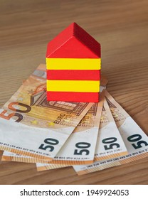 colored house made of wooden cubes on euro banknotes with a wooden background