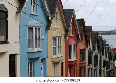 Colored houses of cobh city in ireland. Many sloping houses of all colors are adjoigned along the street.